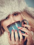 Blonde woman in winter furry hat drinking. Accessories and clothes for cold days, fashion concept. Blonde woman in winter warm furry hat drinking hot drink from Stock Images