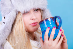 Blonde woman in winter furry hat drinking Royalty Free Stock Image