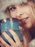 Blonde woman in winter furry hat drinking Stock Photo