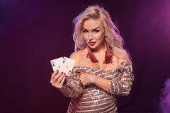 Blonde Woman With A Perfect Hairstyle And Bright Make-up Is Posing With Playing Cards In Her Hands. Casino, Poker. Royalty Free Stock Photography