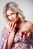 Blonde Woman With Pomegranate On Gray Royalty Free Stock Photos