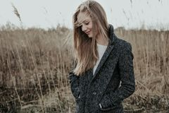 Blonde Woman in wool coat at meadow stock photo