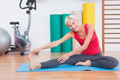 Blonde woman working on exercise mat Stock Image