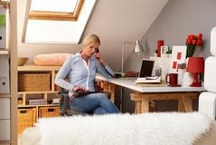 Blonde woman working in homeoffice. Young blonde woman working at home, using tablet, talking on phone Royalty Free Stock Image