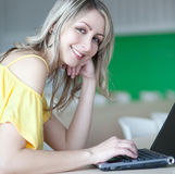 blonde woman working on a laptop Stock Photo