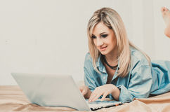 Blonde woman working with laptop on bed Royalty Free Stock Image