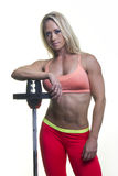 Blonde woman working out. Athletic blonde woman wearing workout clothes leaning on exercise equipment Stock Photo