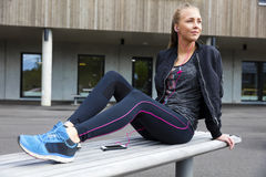 Blonde woman in workout outfit sits outdoor and uses phone Stock Images