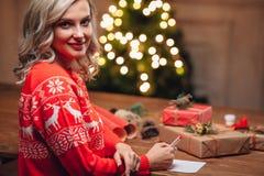 Blonde woman  write on christmas postcard Stock Photo