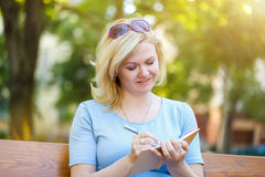 Blonde woman write into notebook outdoor Stock Images