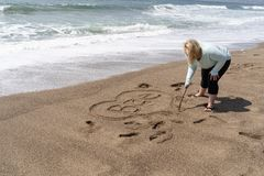 Blonde woman writes Bae slang for Before Anyone Else, representing a romantic relationship in sand on the beach.  royalty free stock photo