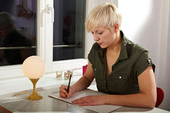 Blonde woman writing a letter Royalty Free Stock Photo