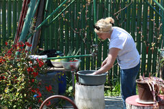 Blonde woman in the yard washing manually the vegetable Royalty Free Stock Image