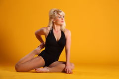 Blonde woman on yellow backdrop doing stretches Stock Image