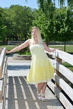 Blonde woman in yellow sundress poses on bridge Stock Photography