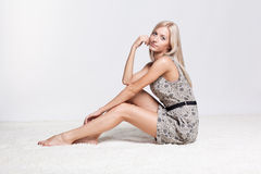 Blonde woman. Blonde young woman sitting on white whole-floor carpet and gray background royalty free stock photos