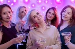 Blonde woman looking at camera while dancing at nightclub. Blonde women looking at camera while dancing at nightclub among her friends Royalty Free Stock Photo