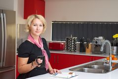Blonde women reading in a kitchen Stock Photography