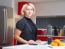 Blonde women in a red kitchen Royalty Free Stock Image