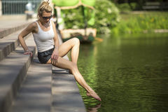 Blonde women sitting on the embankment and touched the water with his foot. Stock Photography