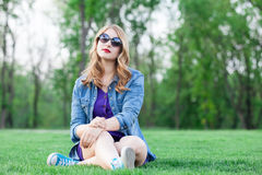 Blonde women sitting on green grass Stock Photos