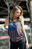 Blonde women is wearing a top featuring the stars and stripes Stock Photo