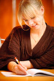 Blonde writes to writing-books Royalty Free Stock Photo