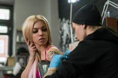 Blonde y amo atractivos del tatuaje en el trabajo en estudio Fotografía de archivo libre de regalías