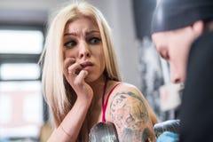 Blonde y amo atractivos del tatuaje en el trabajo en estudio Imágenes de archivo libres de regalías