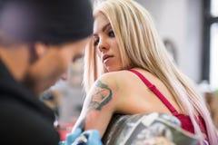 Blonde y amo atractivos del tatuaje en el trabajo en estudio Fotos de archivo libres de regalías