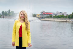 Blonde in a yellow dress against the backdrop fountain Royalty Free Stock Photos