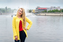 Blonde in a yellow dress against the backdrop fountain Royalty Free Stock Image