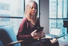 Blonde yound Frau, die modernen Handy in den Händen hält Mädchen, das Finger auf mobilem Schirm der leeren Note auf sonniges zeig Stockbild