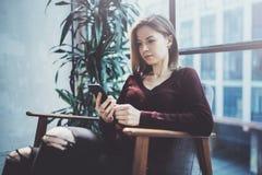 Blonde yound Frau, die modernen Handy in den Händen hält Mädchen, das Finger auf mobilem Schirm der leeren Note auf sonniges zeig Lizenzfreie Stockfotos