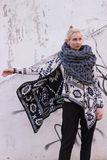 Blonde young beautiful fashion girl wearing aztec black and white jacket and knitted grey vest scarf. Festival outfit. Blonde young beautiful fashion girl Stock Photos