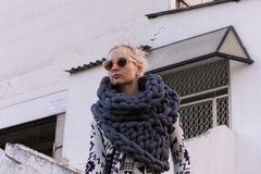 Blonde young beautiful fashion girl wearing aztec black and white jacket and knitted grey vest scarf. Festival outfit. Blonde young beautiful fashion girl Stock Photography