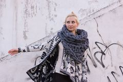 Blonde young beautiful fashion girl wearing aztec black and white jacket and knitted grey vest scarf. Festival outfit. Blonde young beautiful fashion girl Stock Image