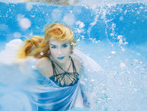 Blonde young beautiful woman as air element underwater Stock Photo