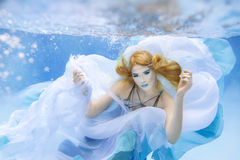 Blonde young beautiful woman as air element underwater Stock Images
