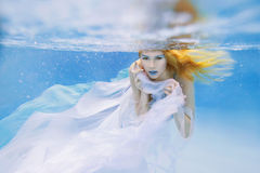 Blonde young beautiful woman as air element underwater Royalty Free Stock Images