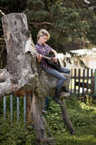 Blonde young country girl sitting on large old stump. And playing on the guitar Stock Photography