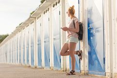 Blonde young female traveler wearing summer style clothing, holding mobile phone, against retro blue beach dressing. Rooms at summer time vacation in Sistiana stock images