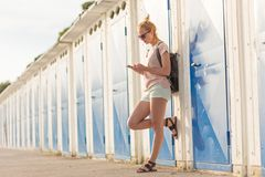 Blonde young female traveler wearing summer style clothing, using mobile phone, leaning against retro blue beach. Dressing rooms at summer time vacation in stock photos