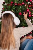 Blonde Girl with ear warmer on head put Christmas red decoration on tree. Blonde young female with white ear warmer on head put Christmas red decoration on big Stock Images