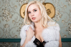 Blonde young girl with big boobs in lingerie and white fur coat posing on a bedroom background Royalty Free Stock Photography