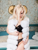 Blonde young girl with big boobs in lingerie and white fur coat posing on a bedroom background Stock Photo