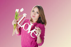 Blonde young girl in blue sweater with decorative word love Stock Photography