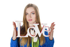 Blonde young girl in blue sweater with decorative word love Royalty Free Stock Photo