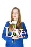 Blonde young girl in blue sweater with decorative word love Royalty Free Stock Photos