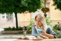 Blonde young girl reading interesting book while drinking coffee outdoors. Wearing white blouse decorated with pearls, shoulders covered with cozy warm grey stock images